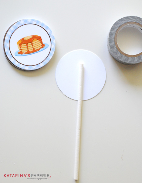 Gluing lollipop sticks to the back of the cupcake toppers